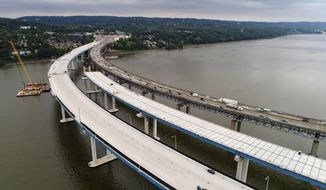 In this July 25, 2017 photo, construction continues on the spans of the new Governor Mario M. Cuomo Bridge, left, as vehicles make their way on the the Tappan Zee Bridge over the Hudson River, near Tarrytown, N.Y. Gov. Andrew Cuomo announced, Thursday, July 27, 2017, that half of the Tappan Zee Bridge replacement will open Aug. 25. It is named for his father, Mario Cuomo, who was governor from 1983 to 1994. (AP Photo/Julie Jacobson)