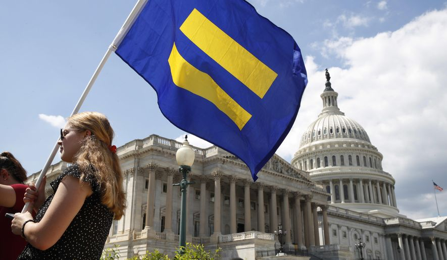 "A supporter of LGBT rights holds up an ""equality flag"" on Capitol Hill in Washington, Wednesday, July 26, 2017, during an event held by Rep. Joe Kennedy, D-Mass. in support of transgender members of the, in response to President Donald Trump's declaration that he wants transgender people barred from serving in the U.S. military ""in any capacity,"" citing ""tremendous medical costs and disruption."" (AP Photo/Jacquelyn Martin)"