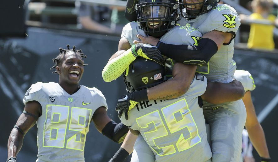 FILE - In this April 29, 2017, file photo, Oregon's Darren Carrington, center right, is congratulated by teammates Kani Benoit (29) Darrian McNeal, top right, after his third touchdown in Oregon's spring NCAA college football game at Autzen Stadium in Eugene Ore. Carrington, dismissed from Oregon two weeks ago soon after he was arrested on a misdemeanor charge of driving under the influence, has signed with Utah. (Collin Andrew/The Register-Guard via AP, File)