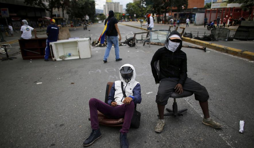 Anti-government demonstrators guard a barricade set up by demonstrators on the second day of a 48-hour general strike in protest of government plans to rewrite the constitution, in Caracas, Venezuela, Thursday, July 27, 2017. Venezuela is less than three days from a vote that would start the process of rewriting its constitution by electing members of a special assembly to reshape the charter. The opposition is boycotting the vote, saying election rules were rigged to guarantee President Nicolas Maduro a majority in the constitutional assembly. (AP Photo/Ariana Cubillos)