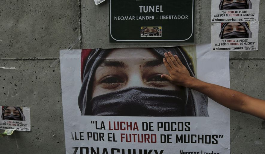 In this Monday, July 24, 2017 photo, a demonstrator touches a poster of Neomar Lander during a tribute to those killed in the recent wave of protests against Venezuela's President Nicolas Maduro, in Caracas, Venezuela. An AP tally of official reports shows that the death toll in nearly 4 months of civil unrest in Venezuela reached 100 on Thursday, July 27, 2017. Most of the deaths reported by the country's chief prosecutor since anti-government protests began in April, that include Lander, are of young men killed by gunfire. The count also includes looters, police allegedly attacked by protesters and civilians killed in accidents related to roadblocks set up during demonstrations (AP Photo/Fernando Llano)