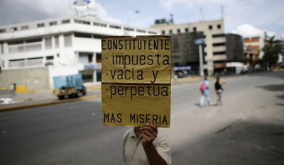 "A man holds up a poster that reads in Spanish: ""Constituent Assembly - Imposed on us, Empty and It perpetuates more poverty"" at a barricade set up by demonstrators on the second day of a 48-hour general strike in protest of government plans to rewrite the constitution, in Caracas, Venezuela, Thursday, July 27, 2017. Venezuela is less than three days from a vote that would start the process of rewriting its constitution by electing members of a special assembly to reshape the charter. The opposition is boycotting the vote, saying election rules were rigged to guarantee President Nicolas Maduro a majority in the constitutional assembly. (AP Photo/Ariana Cubillos)"