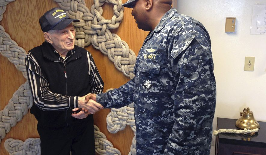 WWII veteran Edmund DelBarone, left, is greeted by Lt. Cmdr. Russell Goff during a tour at Naval Station Newport, in Newport, R.I., Thursday July 27, 2017. DelBarone, a 96-year-old World War II veteran, once dreamed of returning to a Navy installation to reminisce about his naval career, and help of a nonprofit it has become a reality. (AP Photo/Jennifer McDermott)