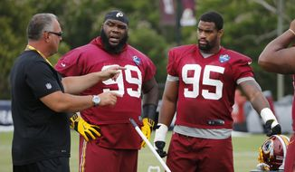 Washington Redskins defensive coordinator, Greg Manusky, left, talks wth defensive tackle Phillip Taylor (99) and defensive end Jonathan Allen (95) during practice at the Washington Redskins NFL training camp in Richmond,. Va., Friday, July 28, 2017. (AP Photo/Steve Helber)