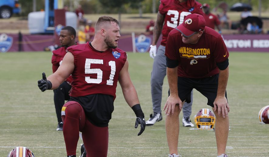 Washington Redskins head coach Jay Gruen, right, talks with inside linebacker Will Compton (51) during practice at NFL football training camp in Richmond, Va., Friday, July 28, 2017. (AP Photo/Steve Helber)