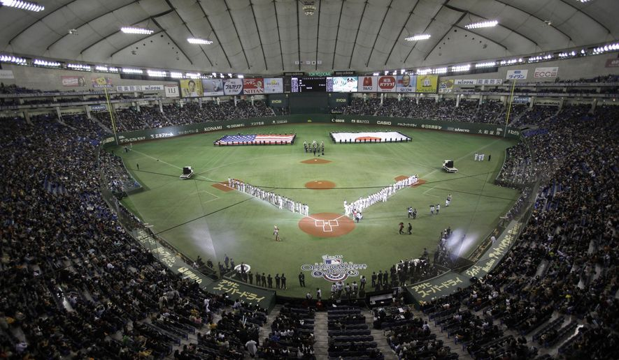 FILE - In this March 28, 2012, file photo, flags of the United States and Japan are carried during the opening ceremony at a season-opening baseball game between the Oakland Athletics and the Seattle Mariners at Tokyo Dome in Tokyo. Major League Baseball plans to start the 2019 and 2020 seasons in Asia and play regular-season games in England in June of both years. The collective bargaining agreement reached in November was finalized and sent to the clubs Friday, July 28, 2017. (AP Photo/Shizuo Kambayashi, File)