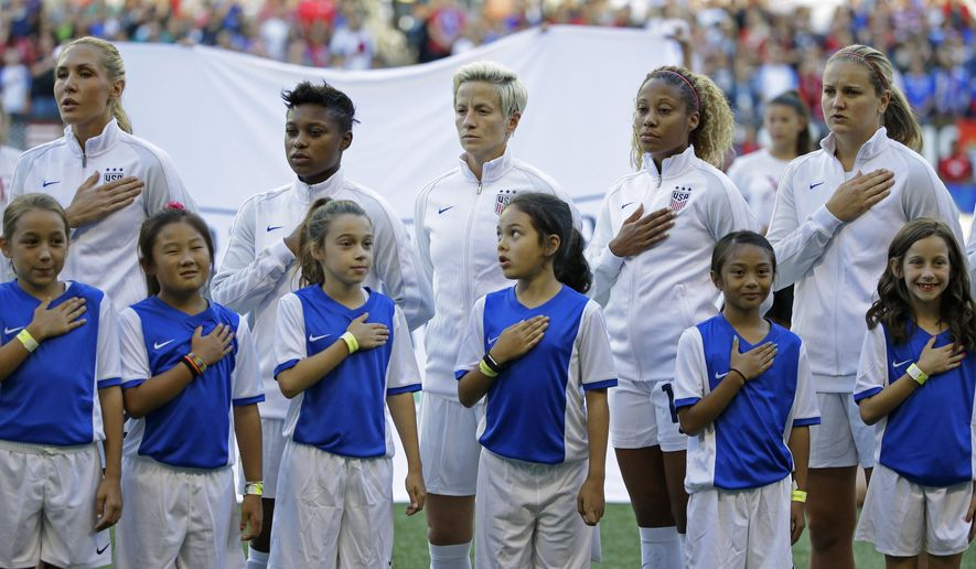 U.S. midfielder Megan Rapinoe, upper center, stands as her teammates and youth escorts hold their hands on their hearts during the singing of the national anthem before the team's Tournament of Nations women's soccer match against Australia, Thursday, July 27, 2017, in Seattle. (AP Photo/Ted S. Warren)