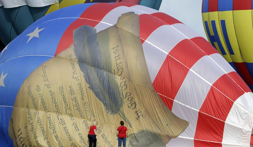Women help deflate a balloon with a painting of the United States Constitution during the first day of the QuickChek New Jersey Festival of Ballooning, Friday, July 28, 2017, in Readington Township, N.J. (AP Photo/Julio Cortez)
