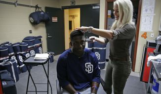 "In this photo taken Thursday, July 20, 2017, hairstylist Lara Albertsen uses a foil trimmer on San Diego Padres' Jose Pirela before the team's baseball game against the San Francisco Giants in San Francisco. The hairstylist based in the East Bay suburb of Danville shows up for the first game of a series to snip for any interested players or coaches and her room has been named ""Big Mac Salon"" after former slugger turned Padres bench coach Mark McGwire paid a visit for a haircut July 20 before the series opener against the Giants. (AP Photo/Eric Risberg)"