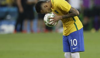 FILE - In this Aug. 20, 2016 file photo, Brazil's Neymar kisses the ball before scoring the decisive penalty kick during the final match of the mens's Olympic football tournament at the Maracana stadium in Rio de Janeiro, Brazil. As Rio de Janeiro reels from corruption, rising crime and unfinished infrastructure, its residents can look no further than the iconic image of Neymar to remind them of the Rio de Janeiro Olympics that took place one year ago and the price they payed for hosting the games.  (AP Photo/Leo Correa, File)
