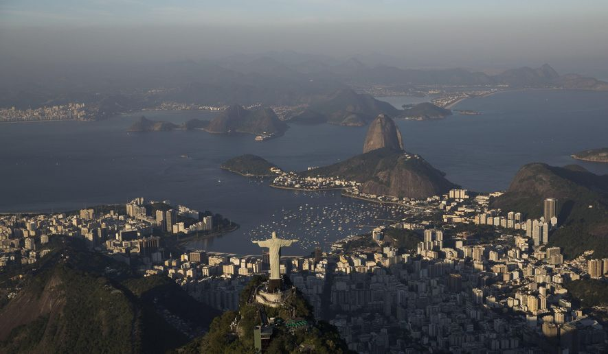 FILE - In this July 4, 2016 file photo, Sugar loaf mountain and Guanabara bay are seen behind the Christ the Redeemer statue in Rio de Janeiro, Brazil. Rio organizers promised to clean up polluted Guanabara Bay in their winning bid in 2009. During the Olympics, officials used stop-gap measures to keep floating sofas, logs, and dead animals from crashing into boats during the sailing events. Since the Olympics, the bankrupt state of Rio de Janeiro has ceased major efforts to clean the bay, with the unwelcome stench usually drifting along the highway from the international airport. (AP Photo/Felipe Dana)