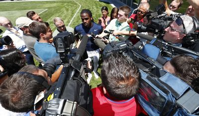 Denver Broncos running back Jamaal Charles, back center, is surrounded by reporters as he talks after taking part in drills at NFL football training camp Friday, July 28, 2017, in Englewood, Colo. (AP Photo/David Zalubowski)