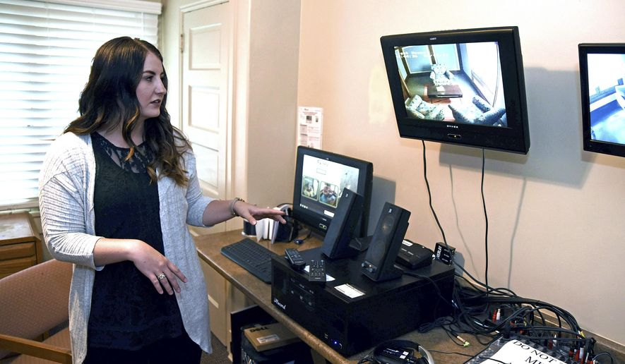 In this Monday July 17, 2017 photo, Anastasia Pili, forensic interviewer for the Children's Justice Center goes over the various equipment in the monitoring room at the center in Ogden, Utah. The space allows for law enforcement involved in a case or the CJC to observe a child's interview as it happens. (Sarah Welliver/Standard-Examiner via AP)