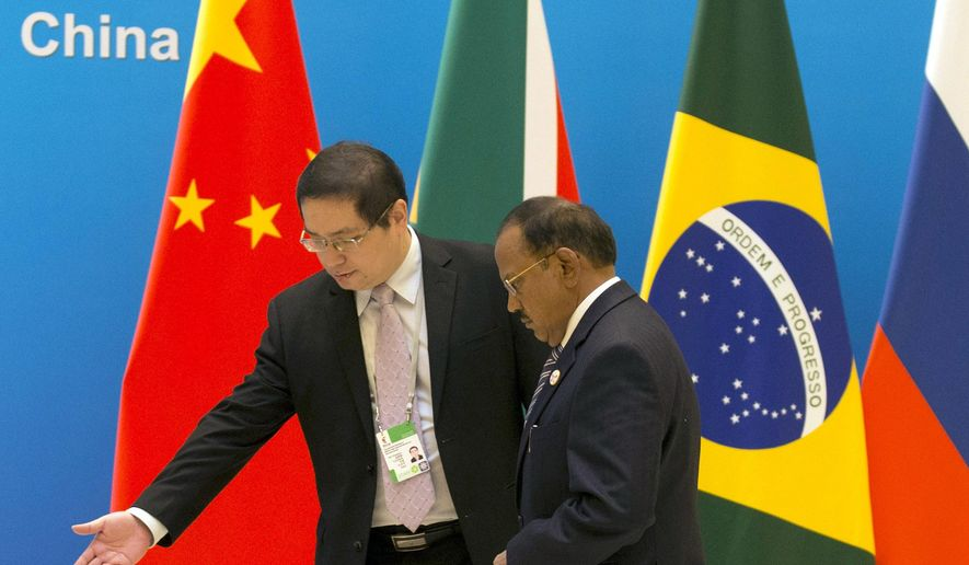 Indian National Security Advisor Ajit Doval, right is shown the way to this position before the seventh meeting of BRICS senior representatives on security issues held at the Diaoyutai state guesthouse near front back to camera in Beijing, China, Friday, July 28, 2017. (AP Photo/Ng Han Guan, Pool)