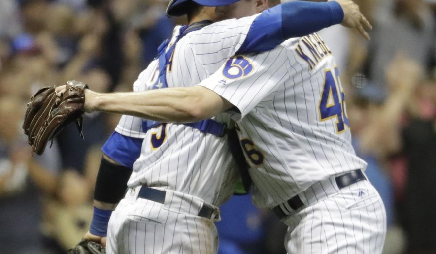 Milwaukee Brewers catcher Manny Pina hugs relief pitcher Corey Knebel after the ninth inning of a baseball game against the Chicago Cubs Friday, July 28, 2017, in Milwaukee. The Brewers won 2-1. (AP Photo/Morry Gash)