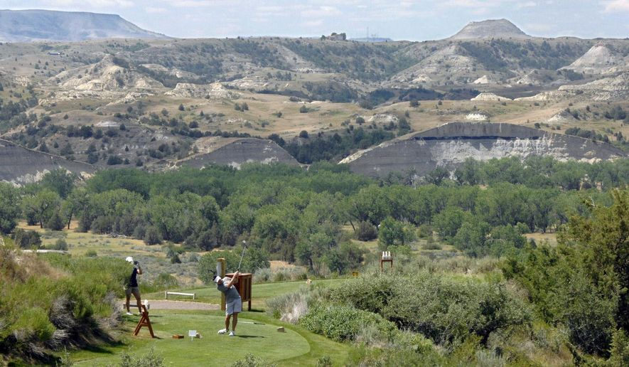 A golfer uses a driver to hit a golf ball from one of the tee boxes perched on a hillside at the Bully Pulpit Golf Course overlooking the Badlands and the Little Missouri River valley in the background earlier this month south of Medora. (Mike McCleary/The Bismarck Tribune via AP)