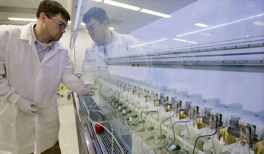 FILE - In this Thursday, Dec.18, 2014, file photograph, scientist Christopher Kistler checks on experiments in AMBR250 bio-reactors in a laboratory at the Merck company facilities in Kenilworth, N.J. Merck & Company, Inc. reports earnings, Friday, July 28, 2017. (AP Photo/Mel Evans, File)