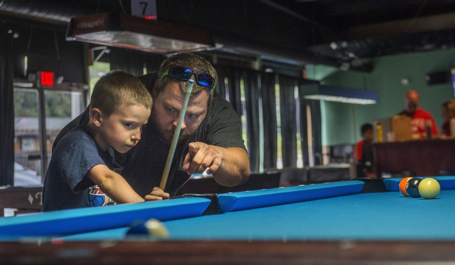 In this June 25, 2017 photo, William Wubben, 6, listens to guidance from Jeff Chase while  playing in a children's billiards league at Racks on the Rocks in West Peoria, Ill. Chase is a co-organizer of the league, designed to introduce children to the sport. (David Zalaznik/Journal Star via AP)
