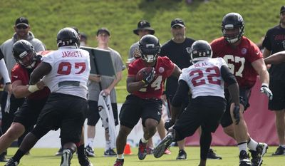 Atlanta Falcons running back Devonta Freeman (24) runs through the line during NFL football training camp Friday, July 28, 2017, in Flowery Branch, Ga.  Falcons have opened training camp without reaching an agreement on a contract extension for running back Freeman, who is entering the final year of his rookie deal.(AP Photo/John Bazemore)