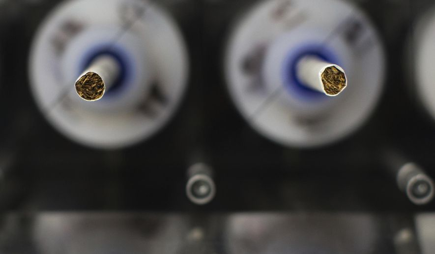 In this Thursday, Nov. 10, 2016 photo, test cigarettes sit in a smoking machine in a lab at the Centers for Disease Control and Prevention in Atlanta. On Friday, July 28, 2017, the U.S. Food and Drug Administration announced that it wants to lower nicotine levels in cigarettes so they aren't so addictive. (AP Photo/Branden Camp)