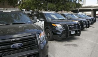 In this Tuesday, July 11, 2017 photo, Austin police Ford utility vehicles are parked on East Eighth Street outside police headquarters in Austin, Texas. The Austin Police Department on Friday, July 28, 2017 pulled nearly 400 Ford Explorer SUVs from its patrol fleet over worries about exhaust fumes inside the vehicles. The move comes as U.S. auto safety regulators investigate complaints of exhaust fume problems in more than 1.3 million Explorers from the 2011 through 2017 model years.(Jay Janner/Austin American-Statesman via AP)