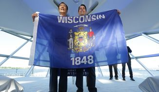 Foxconn Chairman Terry Gou, left, and Gov. Scott Walker hold the Wisconsin flag. In Wisconsin, the Wisconsin flag as well as the U.S. flag is not subject to tax. Other flags are taxable, unless they are bundled with flagpoles. (Associated Press) **FILE**
