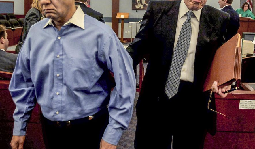 FILE - In this Oct. 11, 2011 file photo, Dr. Dipak Desai, left, leaves court with his attorney Richard Wright during his competence hearing in Las Vegas, Nev. The Nevada Supreme Court Thursday, July 27, 2017, threw out the second-degree murder conviction of Desai, the former Las Vegas physician who died in April in state prison while serving sentences stemming from a 2007 hepatitis C outbreak. (Jeff Scheid/Las Vegas Review-Journal via AP, File)