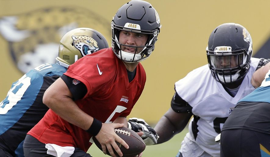 Jacksonville Jaguars quarterback Blake Bortles, center, looks to hand off the ball during a light scrimmage at NFL football training camp, Friday, July 28, 2017, in Jacksonville, Fla. (AP Photo/John Raoux)