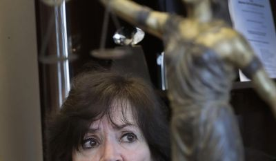 """ADVANCE FOR USE MONDAY, JULY 31, 2017 AND THEREAFTER-In this Wednesday, March 15, 2017 photo, Oakland County Prosecuting Attorney Jessica Cooper speaks during an interview in her office next to her statue of """"Lady Justice"""" in Pontiac, Mich. Cooper argues that all her juvenile lifer cases are rare since they comprise just a small portion of all the criminal cases her office has handled over many years. She is seeking new natural life sentences in 44 of 49 of the county's juvenile lifer cases. (AP Photo/Carlos Osorio)"""
