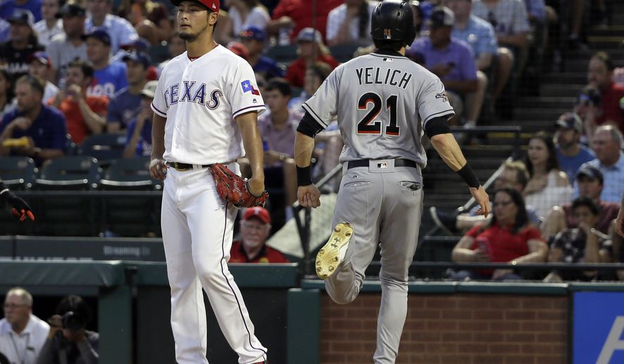 Texas Rangers' Yu Darvish of Japan stands by the plate as Miami Marlins' Christian Yelich (21) scores on a bases clearing triple by Marcell Ozuna in the fourth inning of a baseball game, Wednesday, July 26, 2017, in Arlington, Texas. Ozone's hit also scored Dee Gordon and Giancarlo Stanton. (AP Photo/Tony Gutierrez)