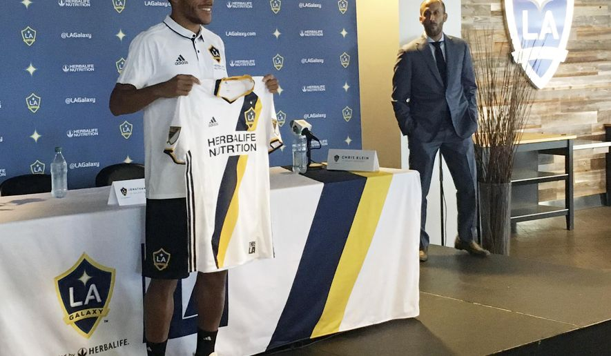 LA Galaxy's new player Jonathan dos Santos holds up a jersey following an MLS soccer press conference  in Carson, Calif. on Friday, July 28, 2017. (AP Photo/Greg Beacham)