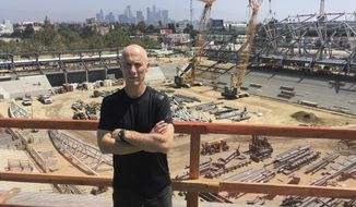 LAFC (Los Angeles Football Club) coach Bob Bradley poses in front of the Los Angeles skyline from the roof of the team's new Banc of California Stadium on Friday, July 28, 2017. The MLS expansion club hired Bradley as its first coach. (AP Photo/Greg Beacham)