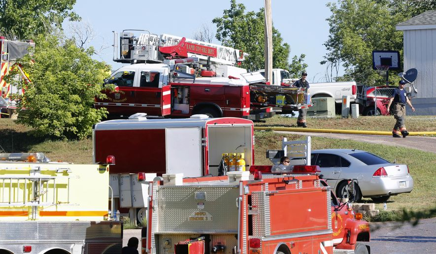 Emergency responders investigate the scene of a mobile home fire, Friday, July 28, 2017 in Rapid City, S.D. A fire official says multiple people are unaccounted after a fire destroyed a mobile home in western South Dakota. (Chris Huber/Rapid City Journal via AP)