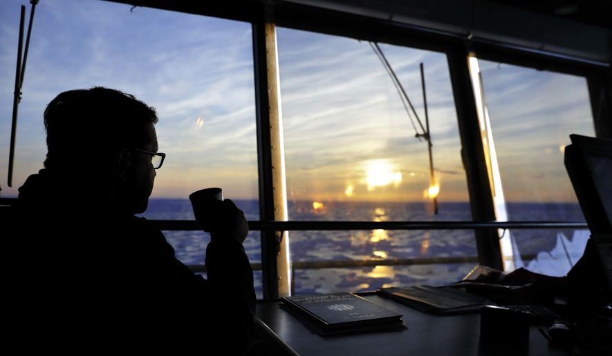 """Sunlight is cast over the sea ice at midnight as Master Mariner Jyri Viljanen, captain of the Finnish icebreaker MSV Nordica, sips a cappuccino while overseeing the navigation of the Northwest Passage through the Victoria Strait in the Canadian Arctic Archipelago, early Saturday, July 22, 2017. Viljanen has been going to sea for 39 years and is making his first transit through the Arctic's Northwest Passage. """"It's once a lifetime,"""" said Viljanen of the opportunity. (AP Photo/David Goldman)"""