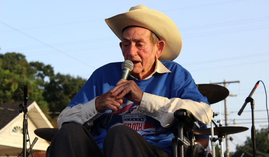 "In this July 2, 2017, photo, Cajun musician D.L. Menard sings at a tribute to him in his home town in Erath, La. Menard, whose song ""The Back Door"" is among the most popular in Cajun music, is dead at the age of 85. Louisiana Funeral Services and Crematory in Broussard said on its website that Menard died Thursday, July 27 at his home in Scott, Louisiana. (Janet McConnaughey via AP)"
