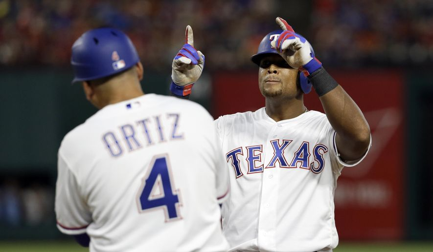 Texas Rangers first base coach Hector Ortiz (4) stands by the bag as Adrian Beltre, right, celebrates his run-scoring single in the fifth inning of a baseball game against the Baltimore Orioles, Friday, July 28, 2017, in Arlington, Texas. The hit was the 2,998th of Beltre's career. (AP Photo/Tony Gutierrez)