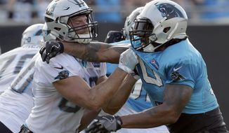 Carolina Panthers' Julius Peppers, right, battles Greg Olsen, left, during practice at NFL football training camp at Wofford College in Spartanburg, S.C., Wednesday, July 26, 2017. (AP Photo/Chuck Burton)