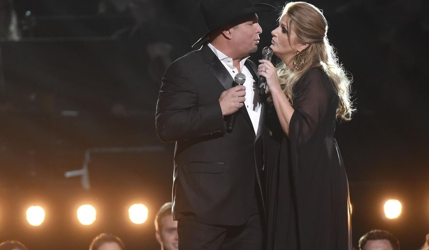 FILE - In this Nov. 2, 2016, file photo, Garth Brooks, left, and Trisha Yearwood perform at the 50th annual CMA Awards at the Bridgestone Arena in Nashville, Tenn. The Lafayette Daily Advertiser reported July 27, 2017, that Brooks and Yearwood bought wedding gifts for a couple who came to a concert in Louisiana last month ahead of their wedding last month. (Photo by Charles Sykes/Invision/AP, File)