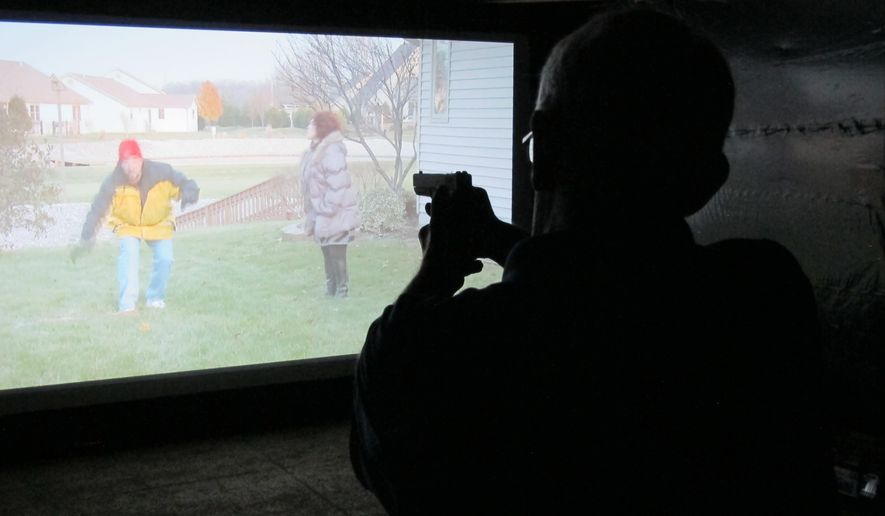 Mark Tulloch, of Kettering, Ohio, takes aim in a firearms training simulator at the Clark County Fair on Wednesday, July 26, 2017, in Springfield, Ohio. The county sheriff rented the simulator to offer as a free exhibit, hoping it will help the public better understand how quickly officers must decide whether to use lethal force. (AP Photo/Kantele Franko)