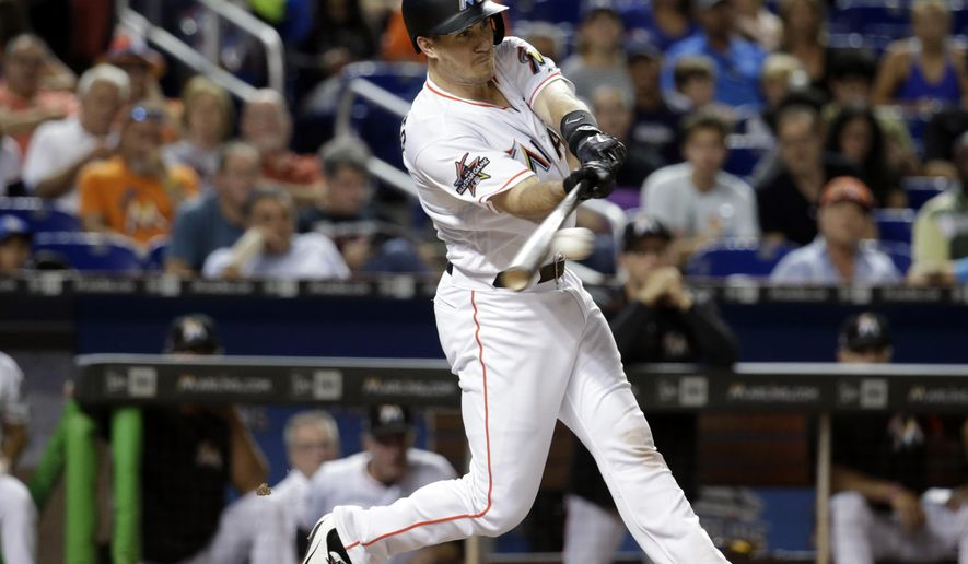 Miami Marlins' J.T. Realmuto hits a single during the fifth inning against the Cincinnati Reds in a baseball game Friday, July 28, 2017, in Miami. (AP Photo/Lynne Sladky)