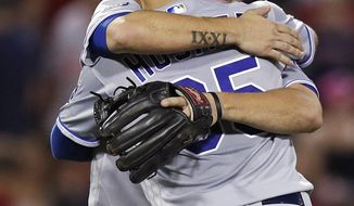 Kansas City Royals third baseman Mike Moustakas, rear, is embraced by first baseman Eric Hosmer (35) after defeating the Boston Red Sox in a baseball game at Fenway Park, Friday, July 28, 2017, in Boston. Moustakas had a three-run home run in the victory. (AP Photo/Charles Krupa)