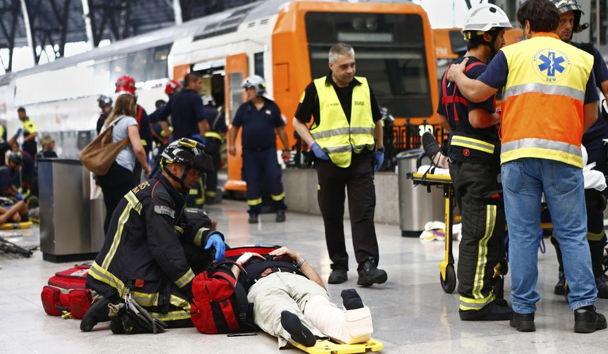 An injured passenger is attended to on the platform of a train station in Barcelona, Spain, Friday, July 28, 2017. Dozens of people were injured when a morning commuter train they were traveling on crashed into the buffers in a station in northeastern Barcelona early Friday. (AP Photo/Adrian Quiroga)