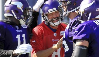 Minnesota Vikings quarterback Sam Bradford (8) is congratulated by teammates Laquon Treadwell (11), Alex Boone (75) and Mike Remmers (72) after throwing a touchdown during NFL football training camp Thursday, July 27, 2017, in Mankato, Minn. (AP Photo/Andy Clayton-King)