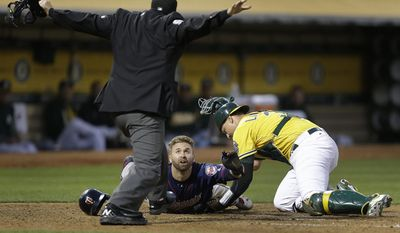 Minnesota Twins' Brian Dozier looks to home plate umpire Mark Ripperger for the call as he scores past Oakland Athletics catcher Ryan Lavarnway, right, during the fourth inning of a baseball game Friday, July 28, 2017, in Oakland, Calif. (AP Photo/Ben Margot)