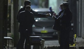 Australian Federal Police and NSW Police officers work in the Surry Hills suburb of Sydney, Australia on Saturday, July 29, 2017. Law enforcement officials raided properties in several Sydney suburbs and arrested four men on suspicion of plotting a terrorist attack related to a bomb plot involving aircraft, officials said. (Sam Mooy/AAP Image via AP)