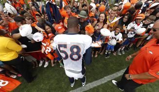 Denver Broncos outside linebacker Von Miller signs autographs for fans after drills at an NFL football training camp, Saturday, July 29, 2017, in Englewood, Colo. (AP Photo/David Zalubowski)