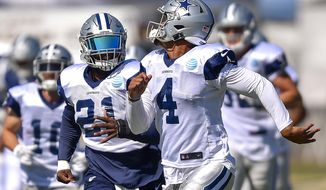 Dallas Cowboys running back Ezekiel Elliott (21) and quarterback Dak Prescott (4) run down the field during calisthenics and looks for a throw during NFL football training camp in Oxnard, Calif., Wednesday, July 26, 2017. (AP Photo/Gus Ruelas)