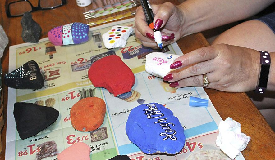 ADVANCE FOR RELEASE SATURDAY, JULY 29, 2017 Tammi Clark joined the Muscatine Rocks group last month and has since left approximately 10 painted rocks at public spaces around Muscaitne, Iowa. (Liora Engel-Smith/Muscatine Journal via AP)
