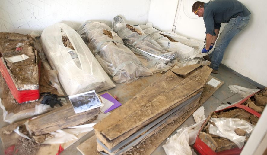 In this Monday, July 17, 2017 photo, George Leader, a professor of sociology and anthropology at the College of New Jersey inspects one of the coffins discovered at a construction site in Philadelphia's Old City, as the remains are fully dug from their coffins and examined at a facility in Burlington County, N.J. The remains were from the former burial ground of Old First Baptist Church, established in 1707, and date from the mid-1700s to the 1860s: three generations, nearly 100 years. (Chris LaChall/Camden Courier-Post via AP)