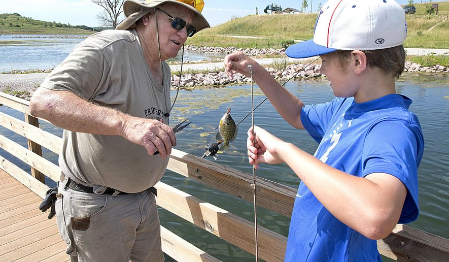Keith Jensen of Hubbard removes a fish from off the hook of grandson Ryder Jones' line while fishing in Kramper Lake at the Danish Alps State Recreation Area Thursday, July 13, 2017. The park is two-years-old and located south of Hubbard, Nebraska. Jones, 12, is from Hickman, Nebraska. (Tim Hynds/Sioux City Journal via AP)